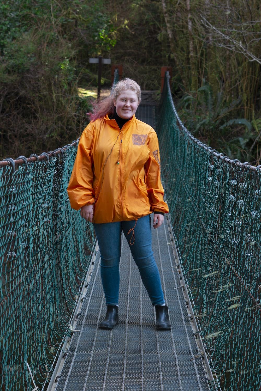 woman in yellow jacket standing on hanging bridge