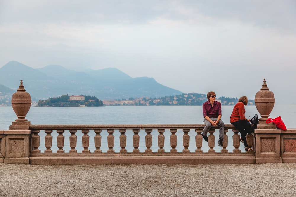 man and woman sitting on white wooden fence near body of water during daytime
