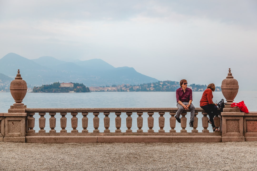 """Two people relaxing in front of """"lago maggiore"""" on the """"Isola Bella"""", beautiful island"""