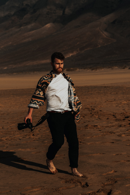 man in black pants holding black camera