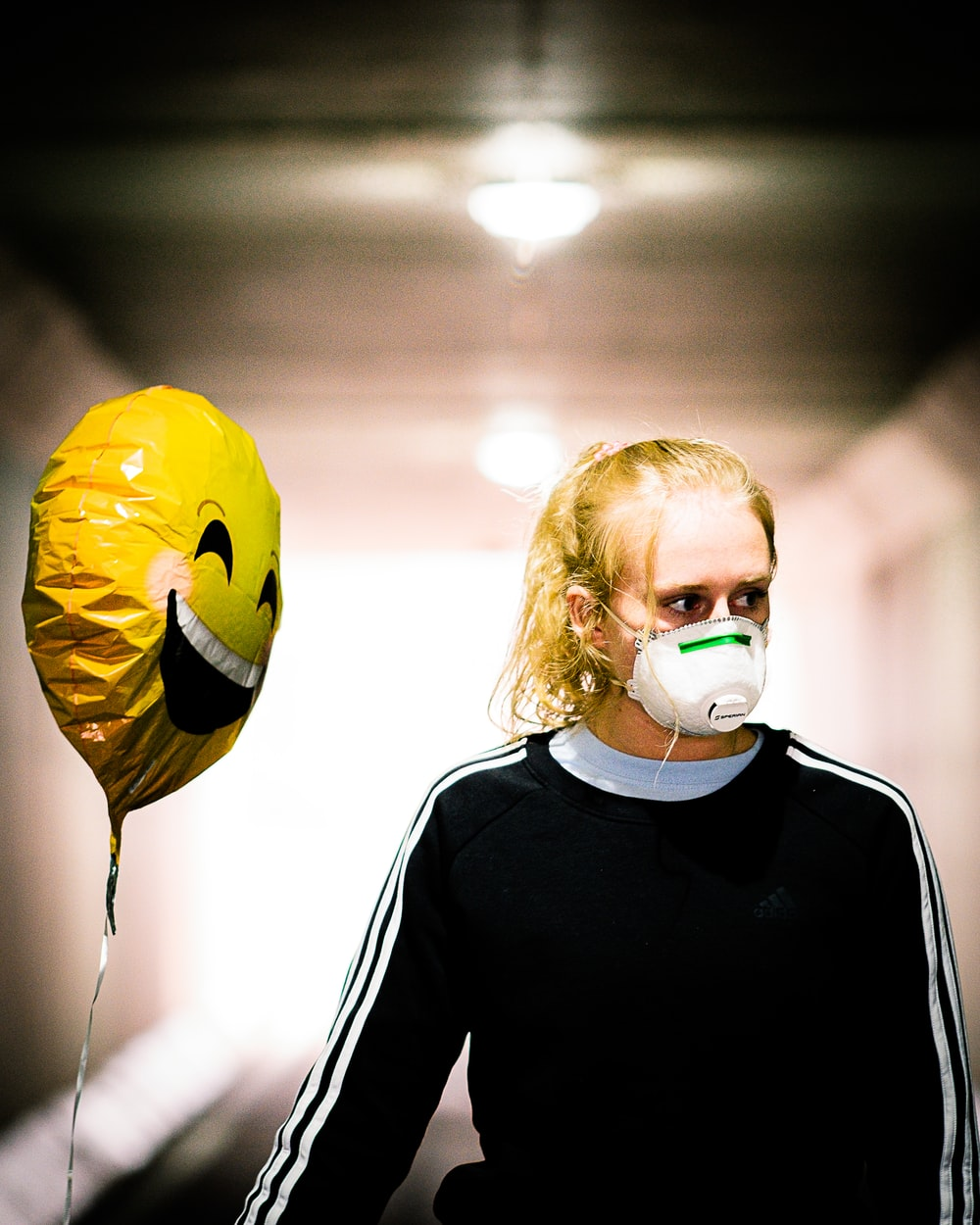 woman in black long sleeve shirt with yellow mask