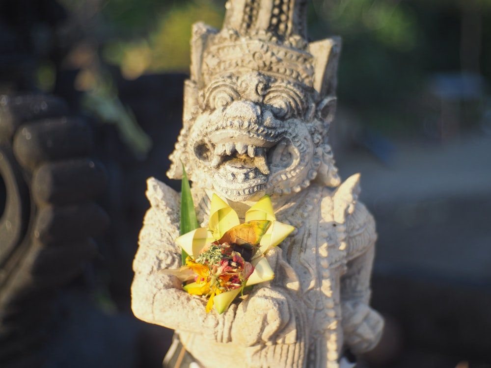 gold dragon with yellow flower on top of it