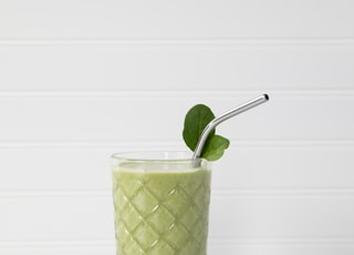 green and white drink with straw in clear drinking glass