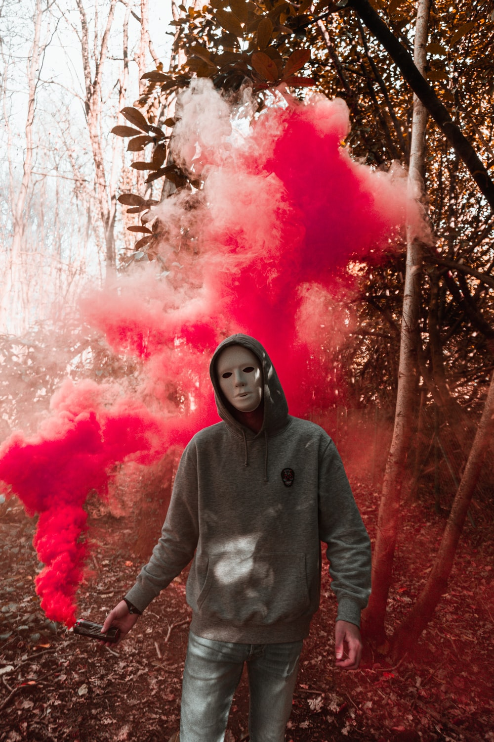 woman in gray hoodie standing in front of pink smoke