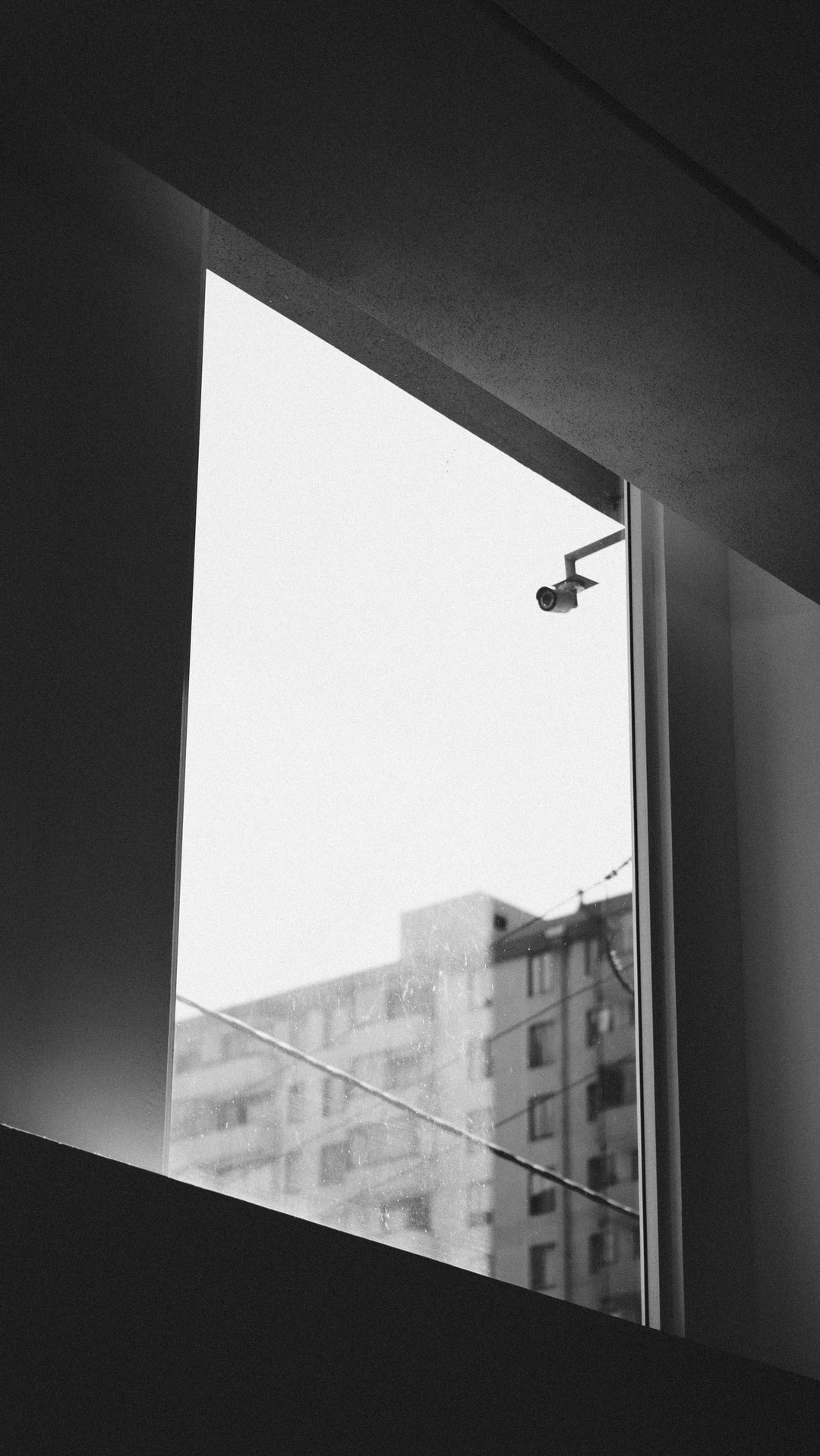 Black and white minimal surveillance camera watching over you.