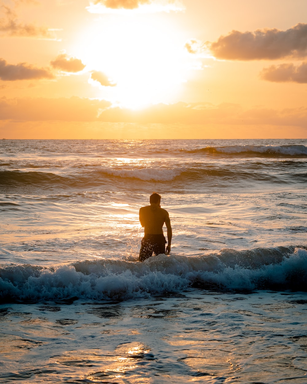 man in black shorts standing on sea waves during sunset