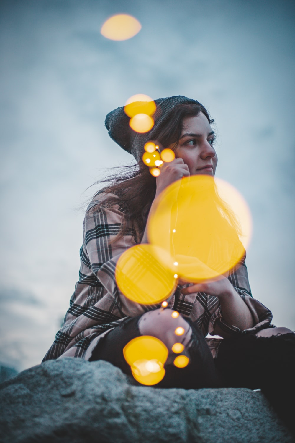 woman in black leather jacket holding yellow balloons