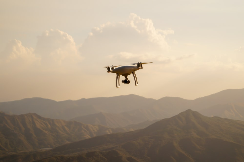 black drone flying over the mountains during daytime
