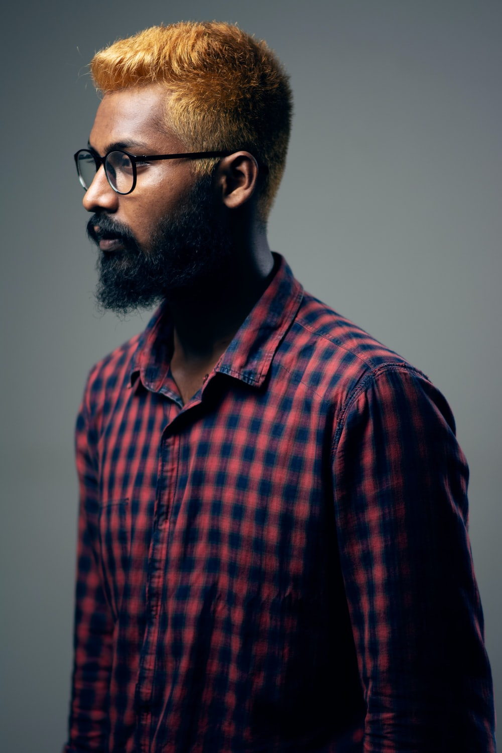 man in red and black plaid button up shirt wearing black framed eyeglasses