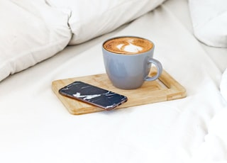 white ceramic mug on brown wooden tray beside black remote control