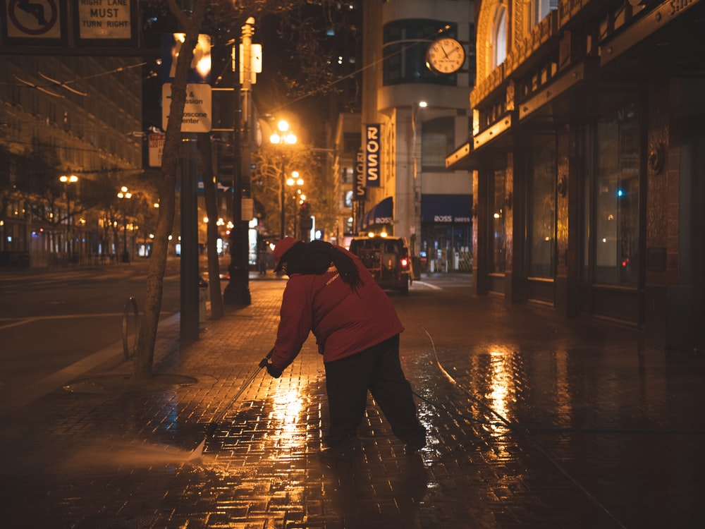 person in red hoodie walking on sidewalk during night time