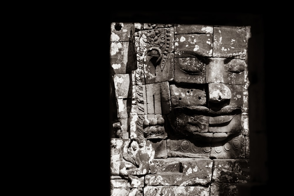 brown concrete wall with face carved