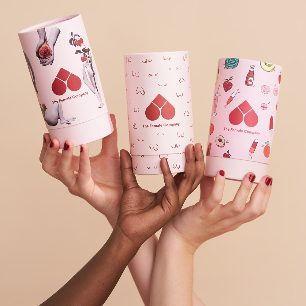 person holding white and pink heart and hearts playing cards