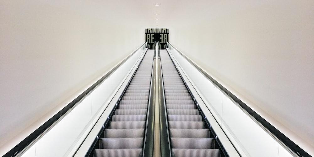 white and black escalator in white room