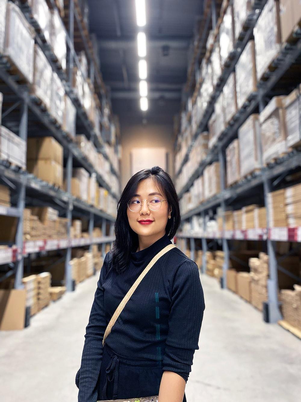 woman in black long sleeve shirt standing near brown wooden shelf