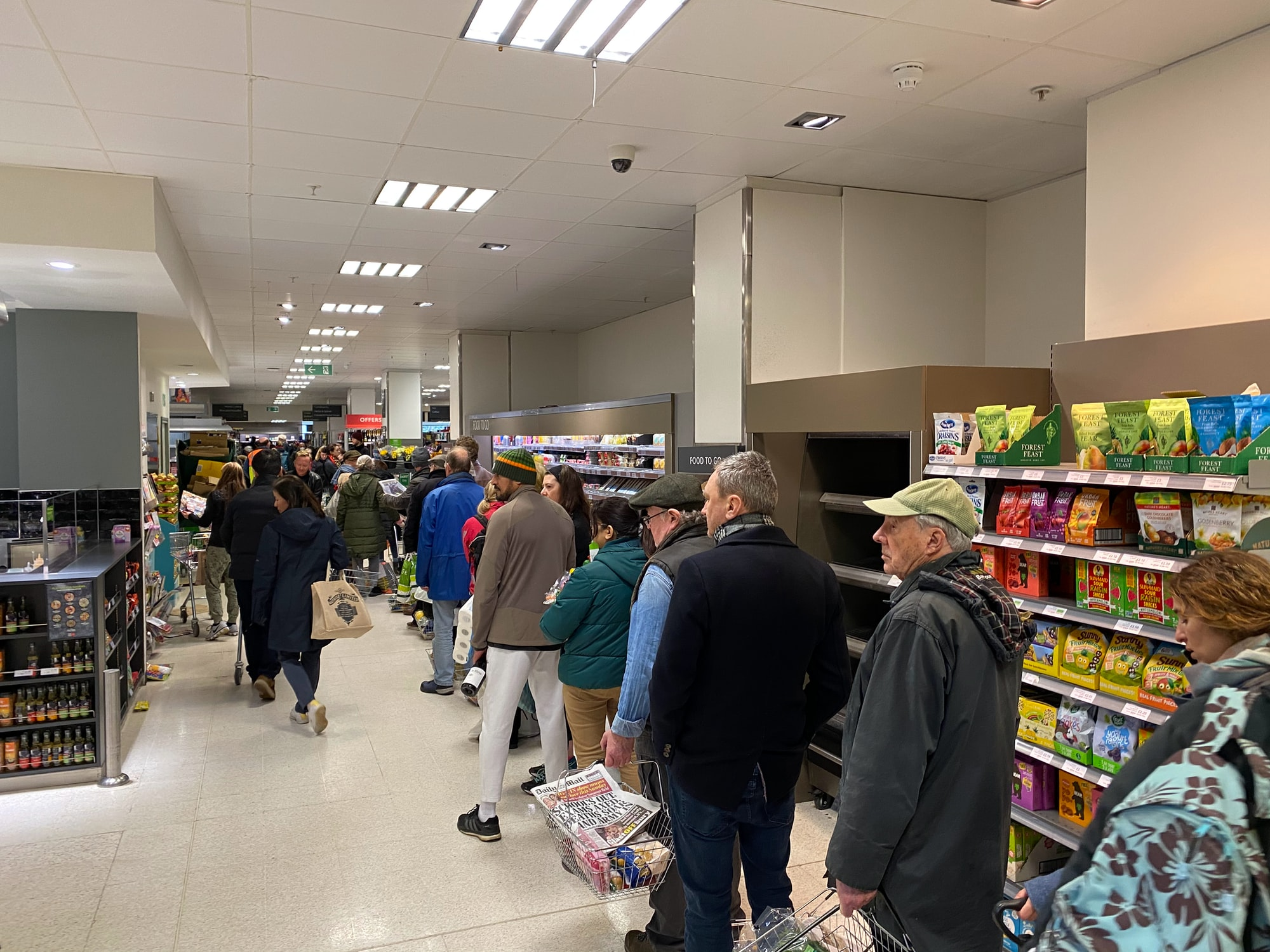 Shoppers patiently wait to pay in Waitrose, as London prepares to lockdown