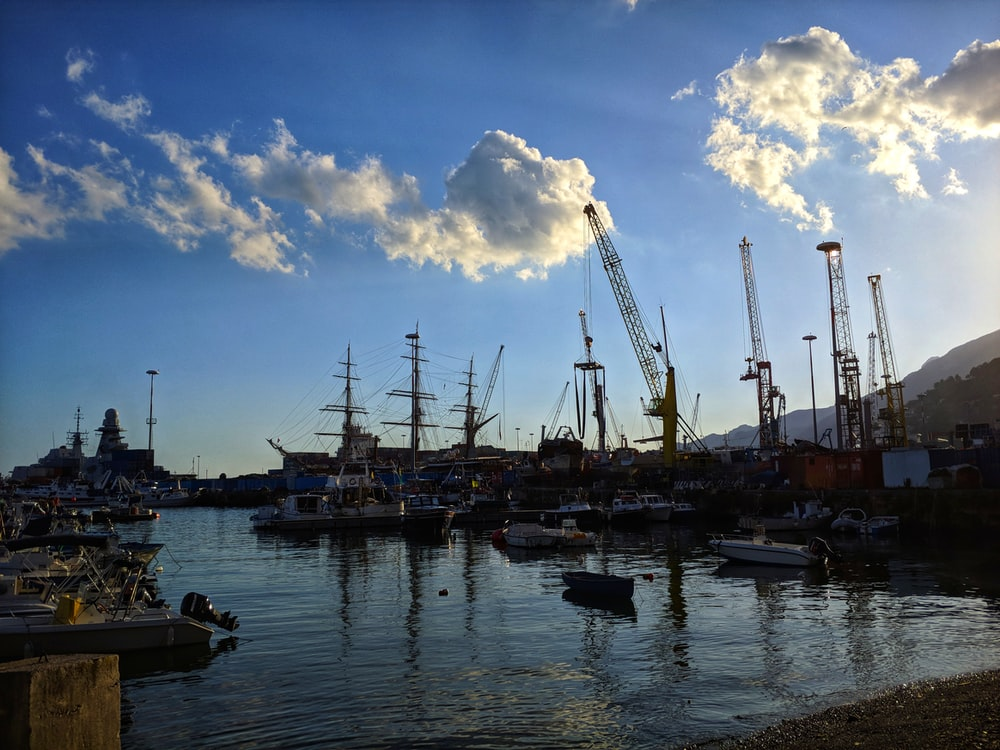 boats on sea under blue sky and white clouds during daytime