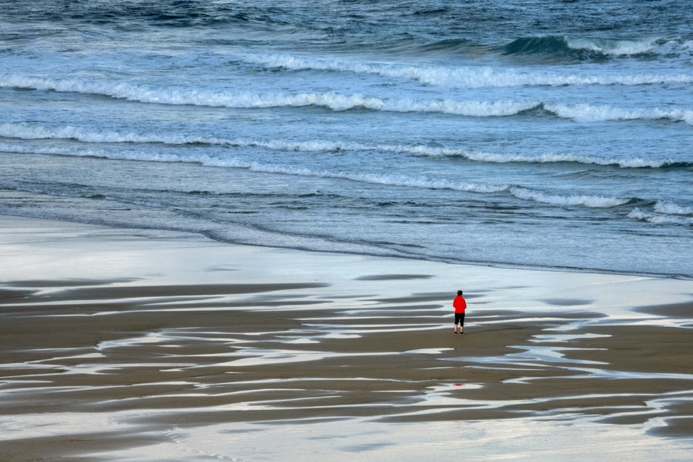 person in red shirt standing on seashore during daytime