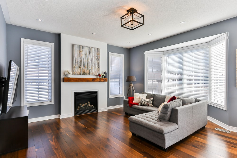gray couch on brown wooden parquet flooring