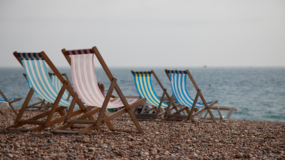 blue and white striped folding chairs on beach during daytime