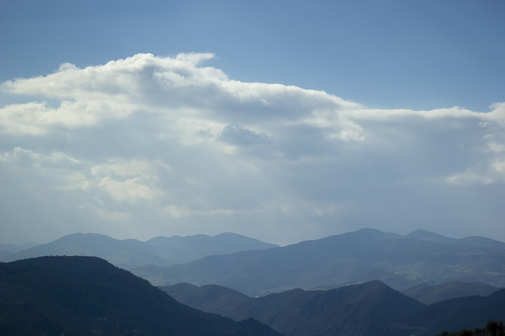 mountains under white clouds and blue sky during daytime