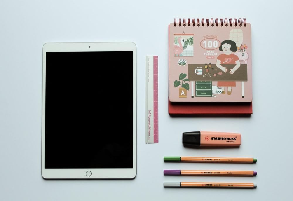 white ipad beside black and pink pen