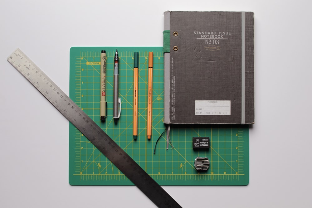 black covered book with pencils and pencils