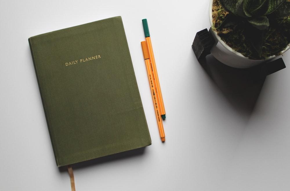 green book beside orange and white pen