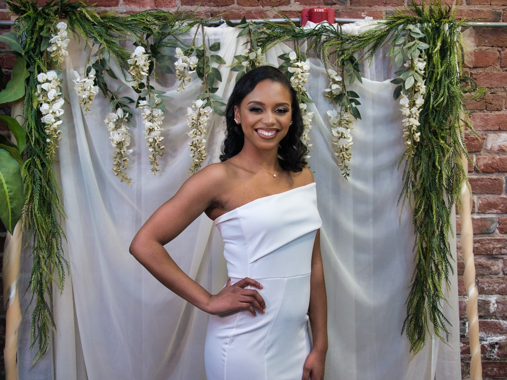 woman in white tube dress standing beside green and white floral curtain