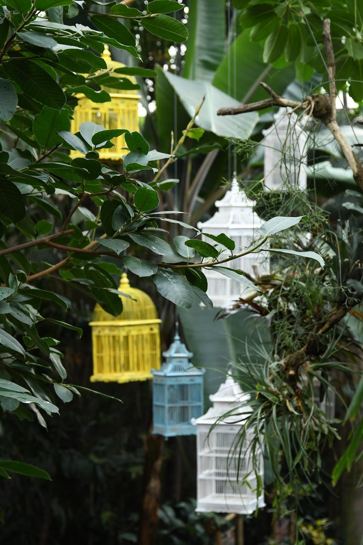 yellow wooden birdhouse on green tree