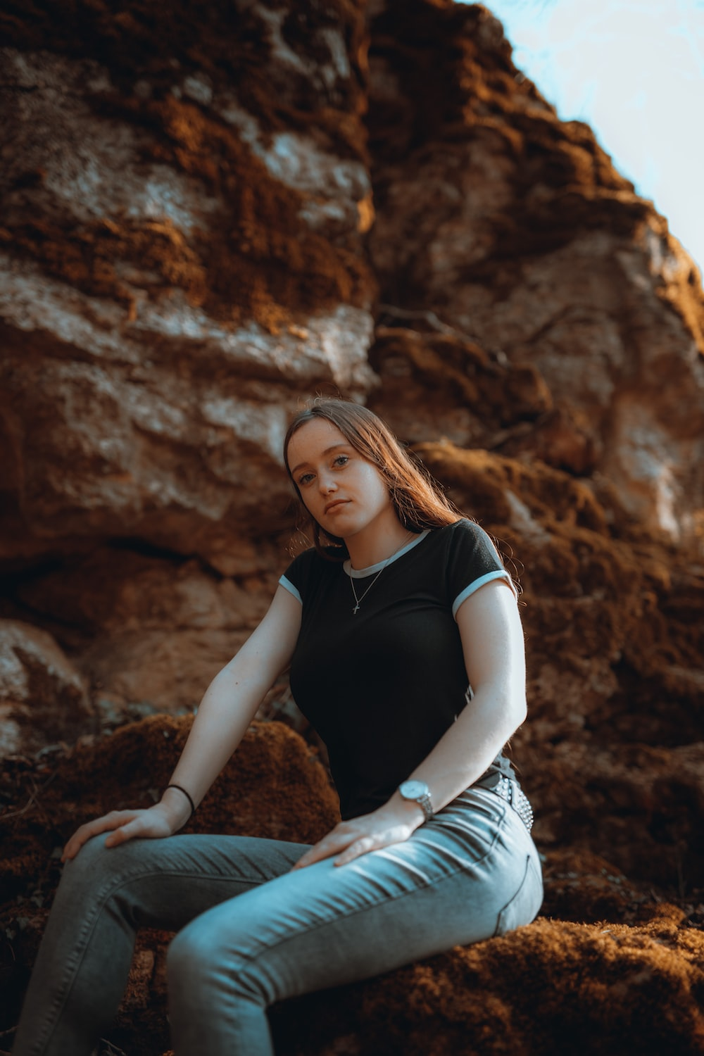 woman in black shirt and white skirt sitting on rock