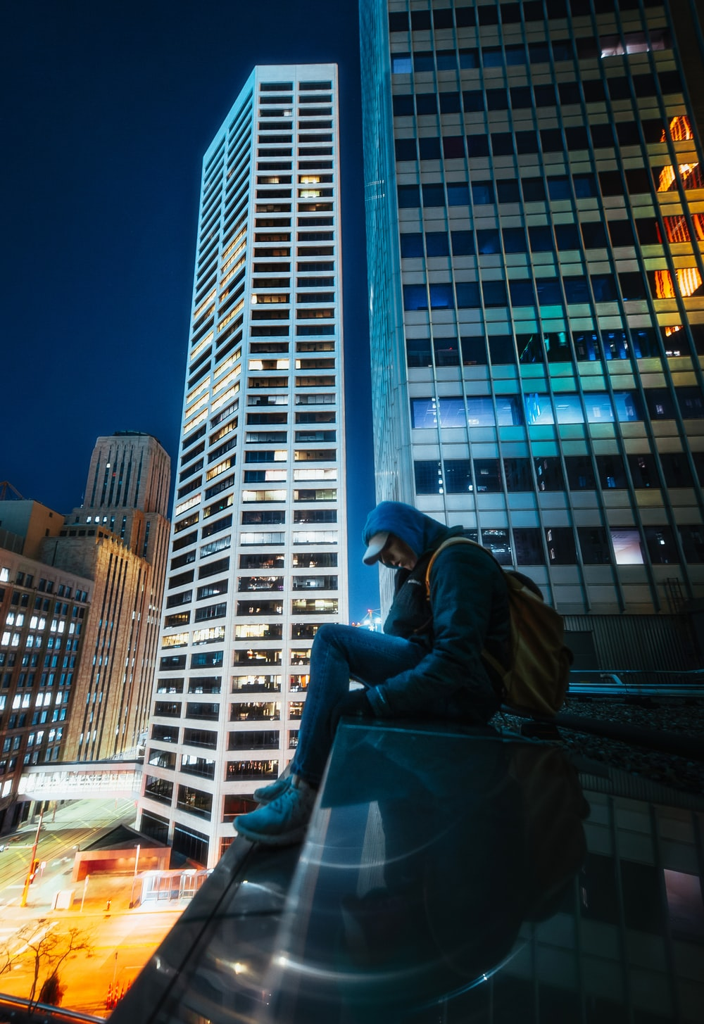 man in black jacket sitting on the edge of a building