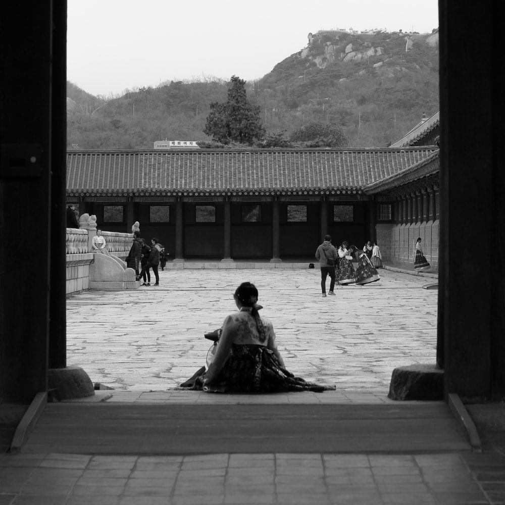 grayscale photo of people sitting on wooden bench