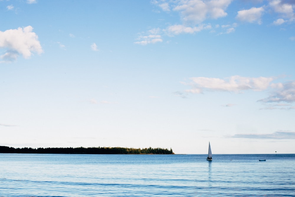 sailboat on sea under blue sky during daytime