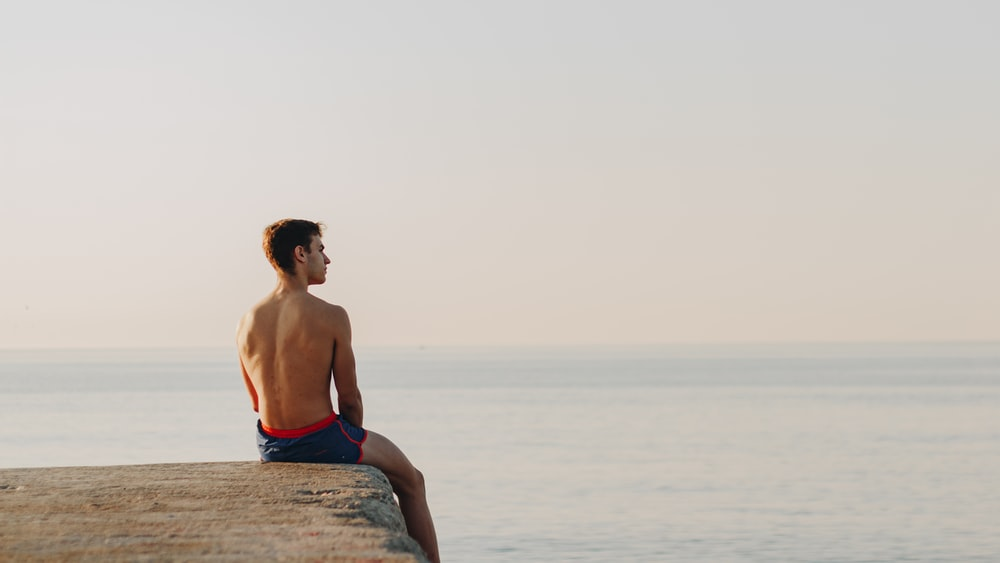 man in blue shorts sitting on rock