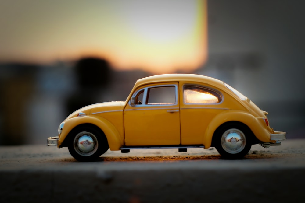 yellow volkswagen beetle on road during daytime