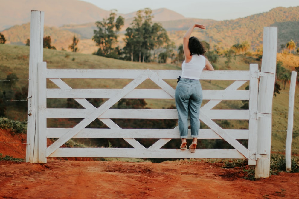 woman in white shirt and blue denim jeans standing on brown dirt road during daytime