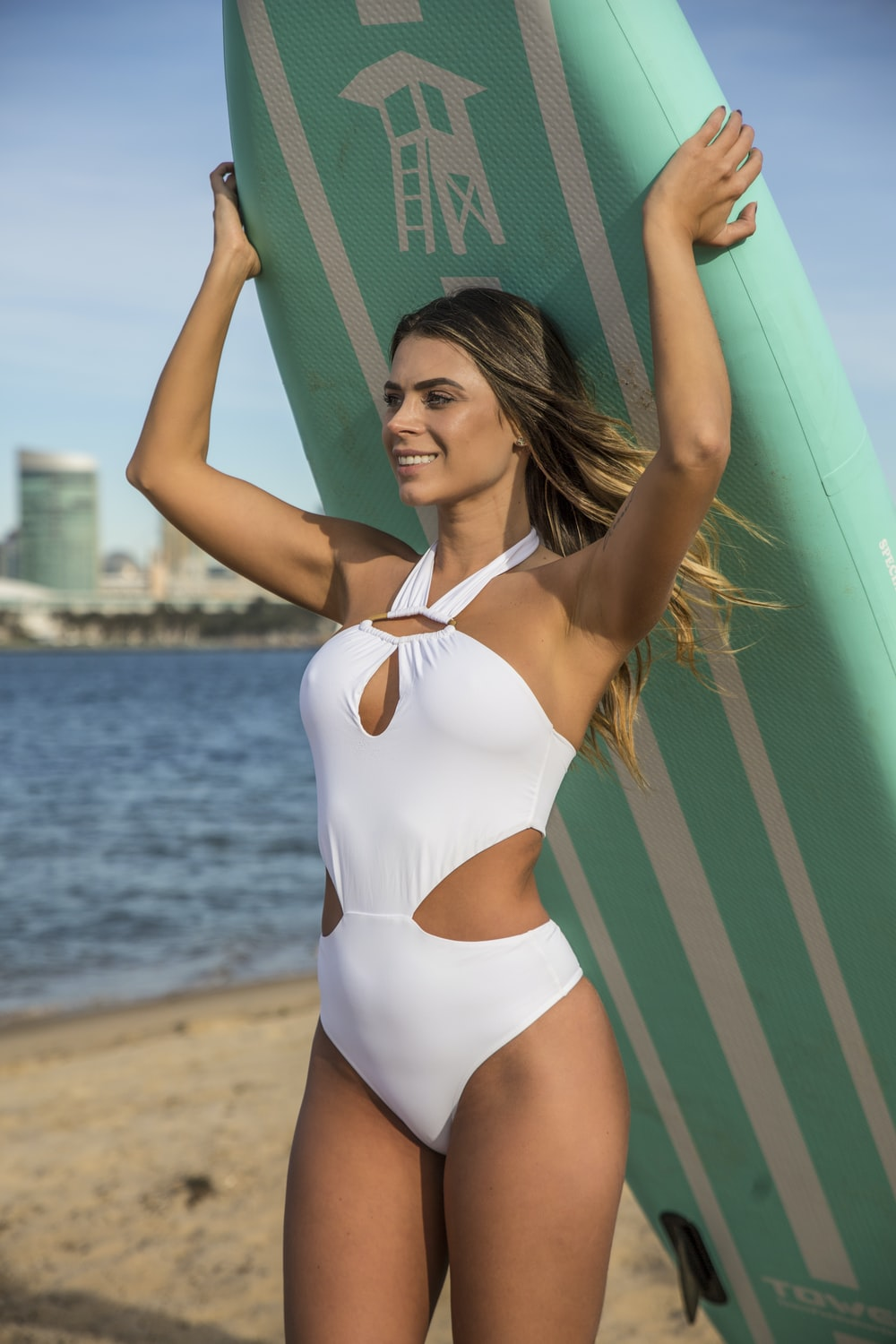 woman in white and blue one piece swimsuit holding green and white striped surfboard during daytime