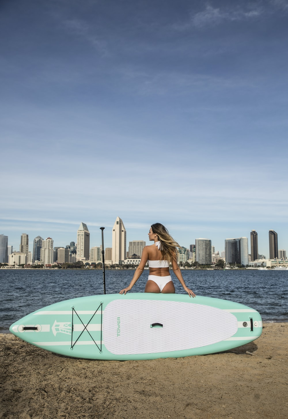 woman in white and blue surfboard on body of water during daytime