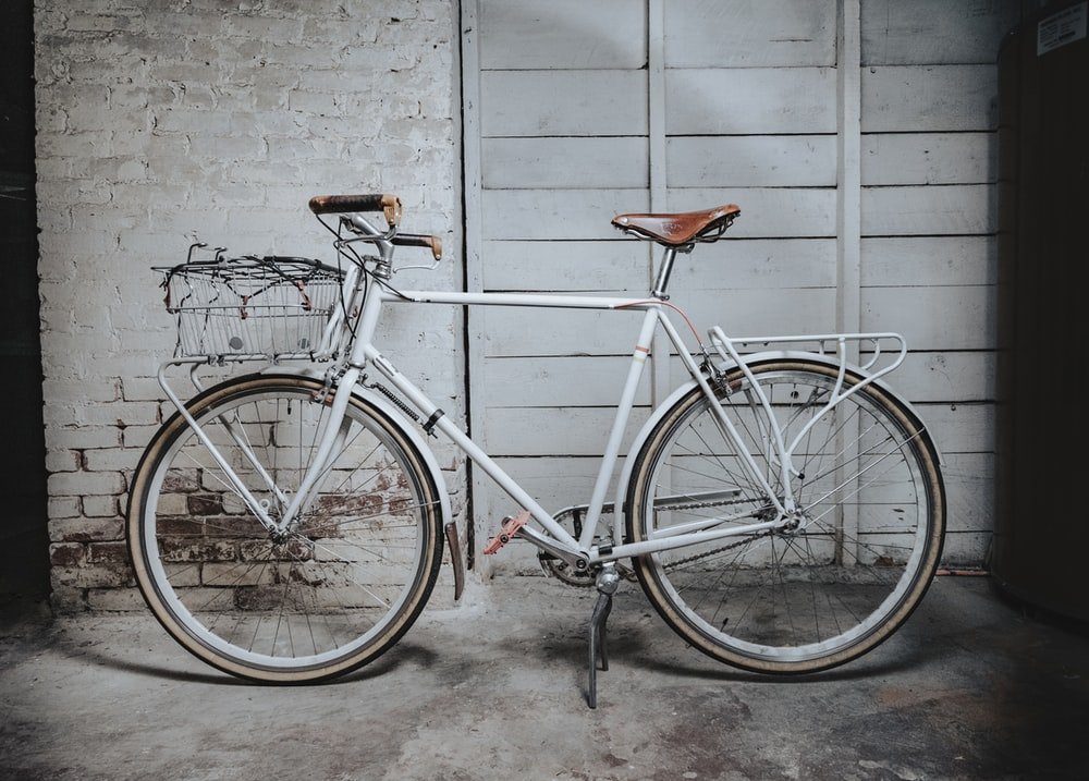 white and brown road bike leaning on gray concrete wall