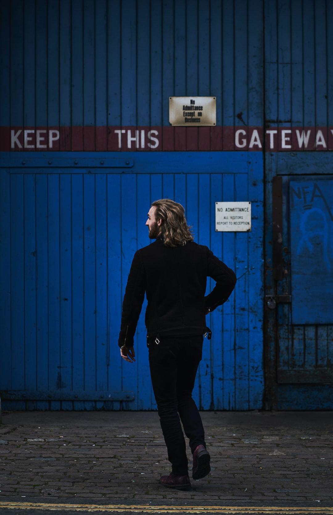 A man walking towards blue door