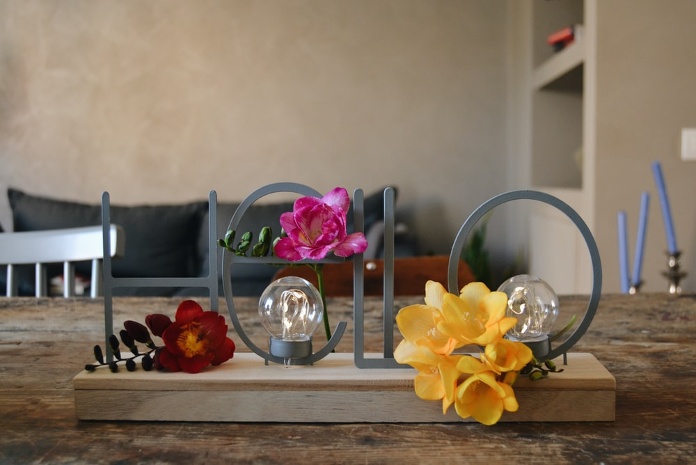 yellow and purple moth orchids in clear glass vase on brown wooden table