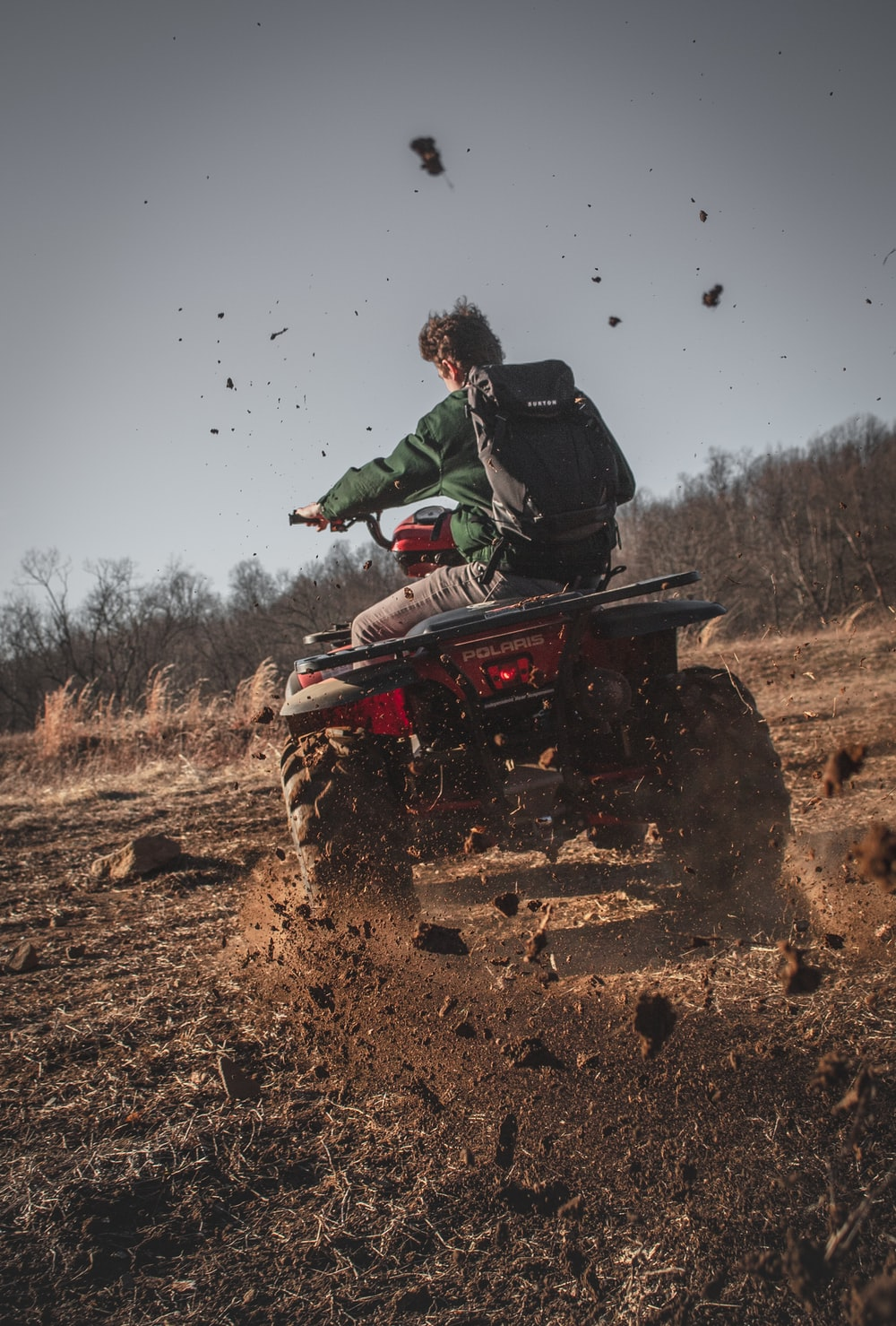 man riding red atv on brown field during daytime