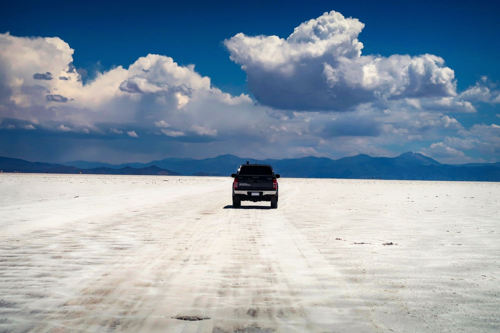 black suv on white sand under white clouds and blue sky during daytime