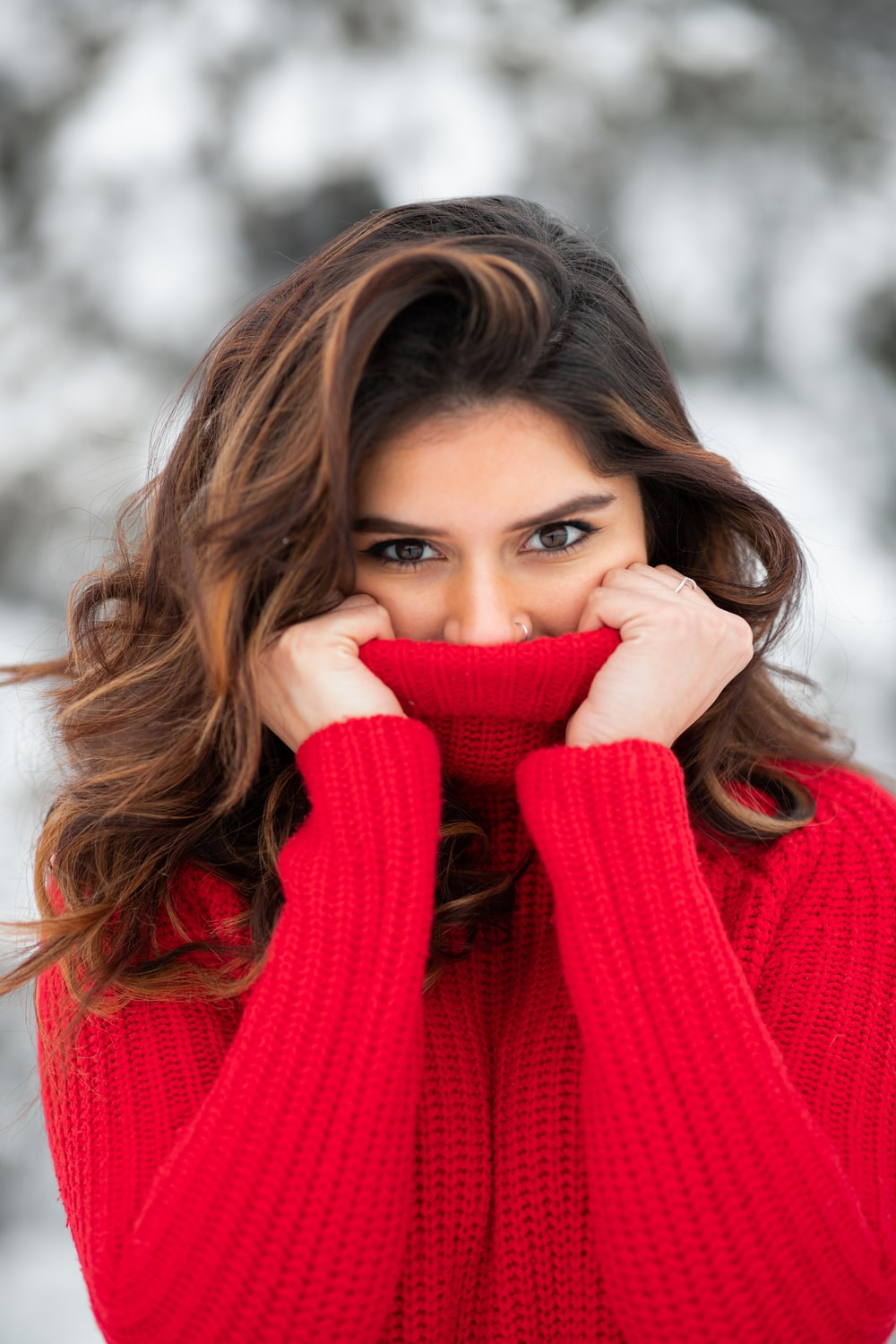 woman in red knit sweater covering her face with her hand
