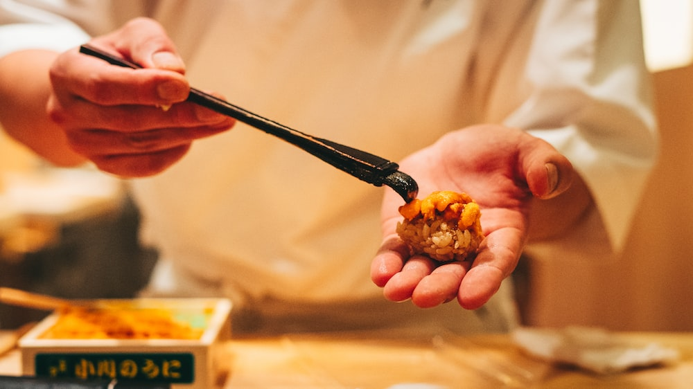 person holding black chopsticks with brown food