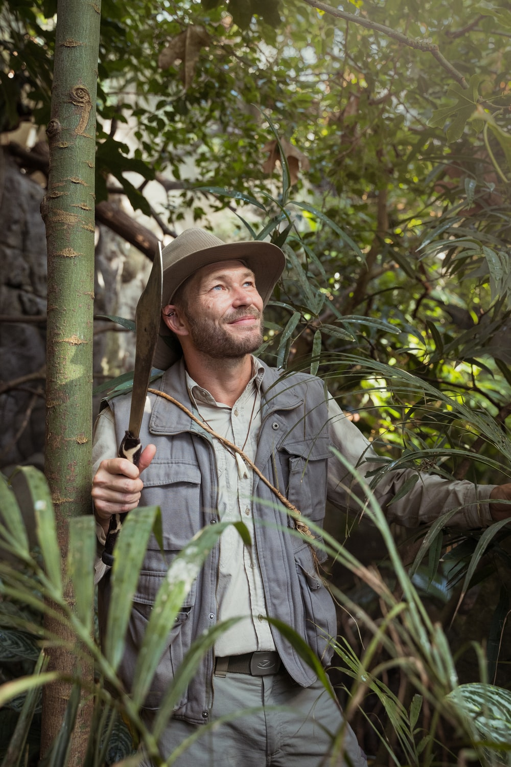 man in gray button up shirt holding green bamboo stick