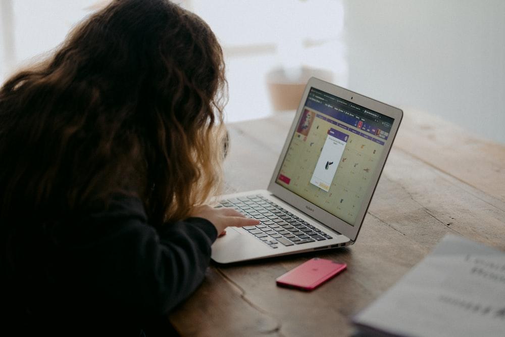 woman in black long sleeve shirt using macbook air