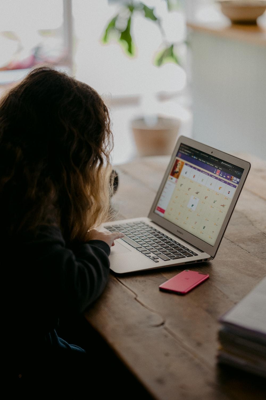 woman in black jacket using macbook air