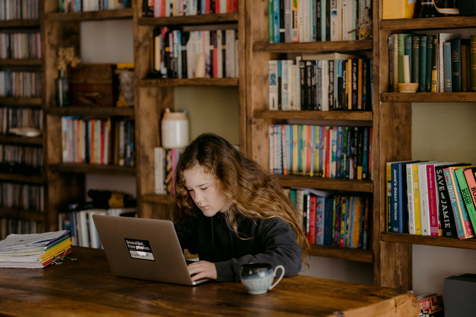 Young teen doing schoolwork at home after UK schools close due to the Coronavirus.